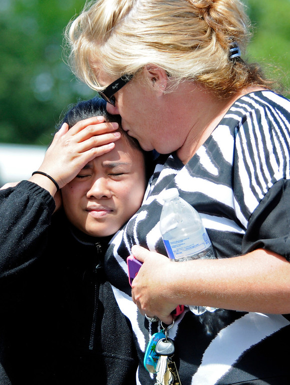 . A student is kissed after arriving at the Fred Meyer grocery store parking lot in Wood Village, Ore.,  after a shooting at Reynolds High School Tuesday, June 10, 2014, in nearby Troutdale.  (AP Photo/Greg Wahl-Stephens)