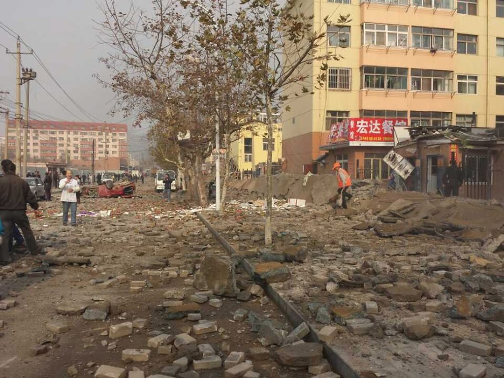 . A general view of the disaster scene after an explosion on an oil pipeline in Qingdao in east China\'s Shandong province 22 November 2013. At least 35 people were killed and more are injured in the morning accident.  EPA/YU Fangping