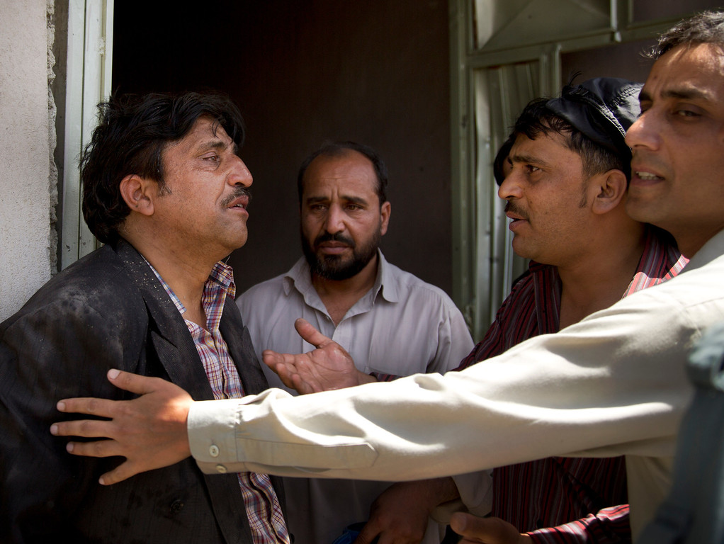 . Afghans comfort a man, left, who claims he has lost all his children at the scene where a suicide car bomber attacked a NATO convoy in Kabul, Afghanistan, Thursday, May 16, 2013.  (AP Photo/Anja Niedringhaus)