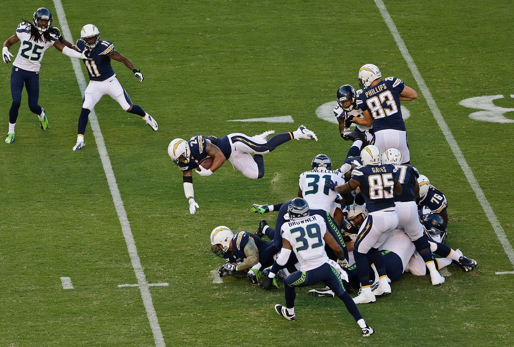 . San Diego Chargers running back Ryan Mathews sails over the Seattle Seahawks defense to gain a first down in the first quarter of an NFL preseason football game Thursday, Aug. 8, 2013, in San Diego. (AP Photo/Lenny Ignelzi)