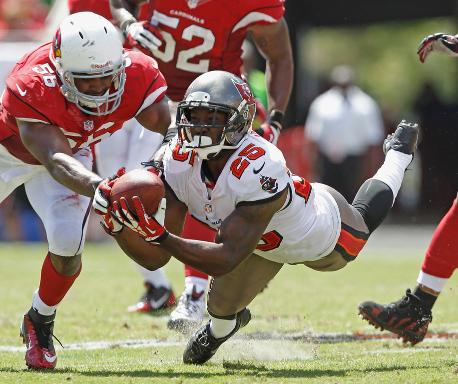 . TAMPA, FL - SEPTEMBER 29:  Mikes James #25 of the Tampa Bay Buccaneers makes a diving catch against Karlos Dansby #56 of the Arizona Cardinals during the 2nd quarter at Raymond James Stadium on September 29, 2013 in Tampa, Florida. ( Photo by Scott Iskowitz /Getty Images)