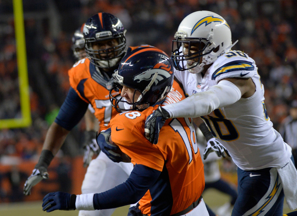 . DENVER, CO - DECEMBER 12: Denver Broncos quarterback Peyton Manning (18) gets sacked by San Diego Chargers strong safety Marcus Gilchrist (38) during the second quarter. The Denver Broncos vs. the San Diego Chargers at Sports Authority Field at Mile High in Denver on December 12, 2013. (Photo by Joe Amon/The Denver Post)