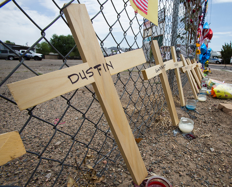 . Crosses with the names of the deceased lean on a fence outside Fire Station 7 in Prescott, Ariz. on Tuesday, July 2, 2013 in a makeshift memorial for the 19 Granite Mountain Hotshots who were killed by an out-of-control blaze near Yarnell, Ariz. on Sunday. (AP Photo/The Arizona Republic, Tom Tingle)