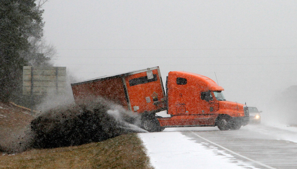 . A truck slides off the road as it tries to avoid another wrecked truck as snow begins to accumulate on Interstate 65 near Clanton, Ala., Tuesday, Jan. 28, 2014. The southern half of Alabama shut down Tuesday because of a rare storm that left a slippery layer of ice and snow across a region unaccustomed to dealing with the wintry threat. (AP Photo/Butch Dill)