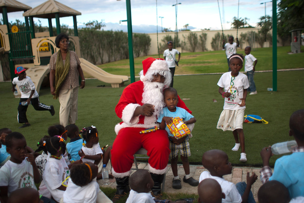 . A man disguised as Santa Claus poses for pictures with a boy during a Christmas gift distribution at the U.S. Embassy in Port-au-Prince, Haiti, Sunday Dec. 23, 2012. (AP Photo/Dieu Nalio Chery)