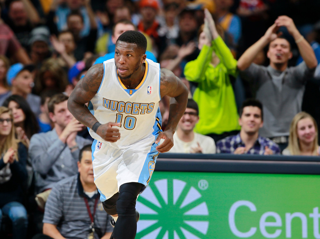 . Fans applaud for Denver Nuggets guard Nate Robinson, front, after he hit a basket against the New Orleans Pelicans in the fourth quarter of the Nuggets\' 102-93 victory in an NBA basketball game in Denver on Sunday, Dec. 15, 2013. (AP Photo/David Zalubowski)