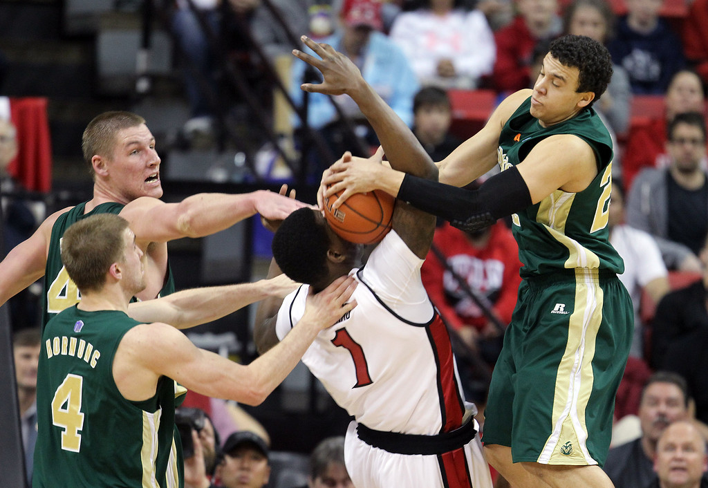 . UNLV\'s Quintrell Thomas, center, tries to pull down a rebound between Colorado State\'s Colton Iverson, left rear, Pierce Hornung (4) and Dorian Green (22) during the first half of an NCAA college basketball game Wednesday, Feb. 20, 2013, in Las Vegas. (AP Photo/Isaac Brekken)