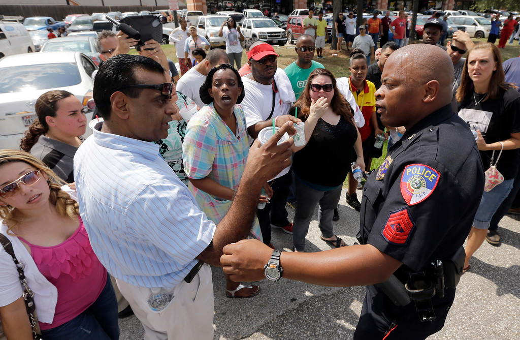 . A law enforcement officer explains how parents can pickup their children outside Spring High School Wednesday, Sept. 4, 2013, in Spring, Texas, after 17-year-old student was stabbed to death and three others were injured after a fight at the Houston-area high school.(AP Photo/David J. Phillip)