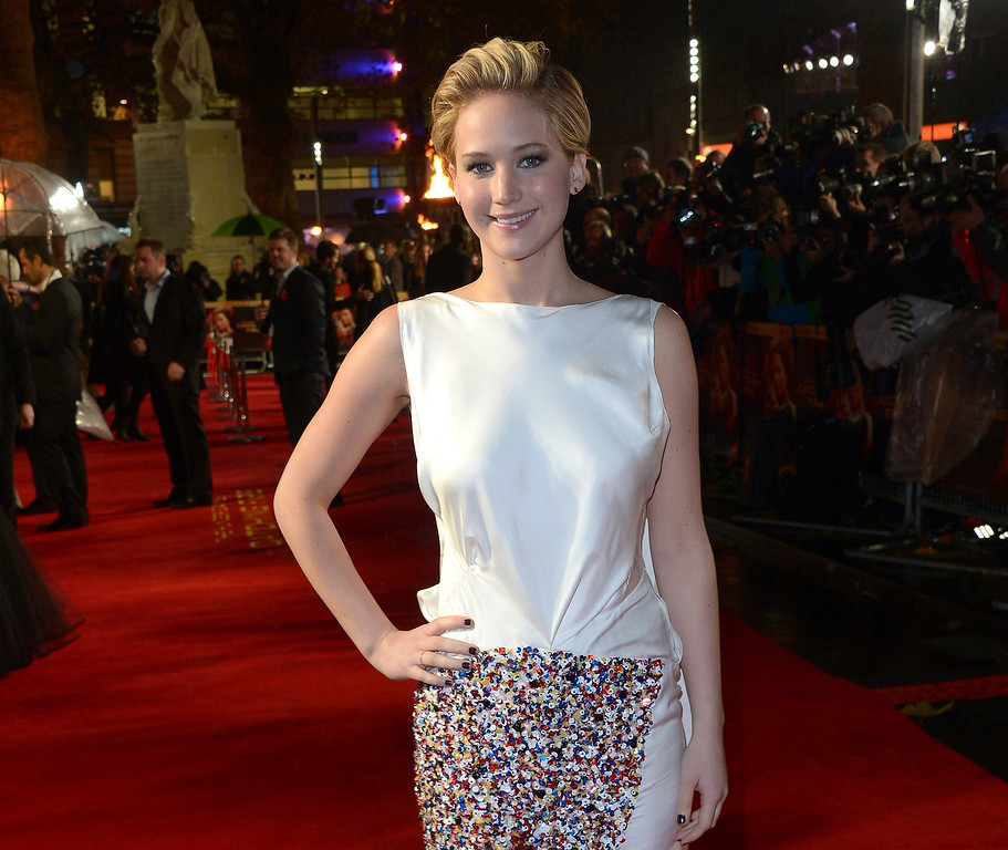 """. American actress Jennifer Lawrence poses for photographers as she arrives on the red carpet for the World Premiere of \""""The Hunger Games: Catching Fire,\"""" on Monday Nov. 11,  2013, in Leicester Square, London. Lawrence will not only star in the upcoming film adaptation of Jeanette Wallsí 2005 best-selling memoir ìThe Glass Castle,î the project will also mark her first time as a producer.  A production date for the movie has not yet been set. (Photo by Jon Furniss/Invision/AP)"""
