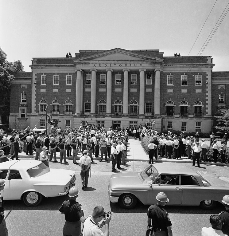 . Large crowds of newsmen and law enforcement officers crowd the front of Foster Auditorium of the University of Alabama campus, June 11, 1963 in Tuscaloosa, Ala., as Gov. George Wallace barred entrance of two black students. Armed patrolmen stand guard on the roof of the building. The two students wait in the car in right foreground. (AP Photo)