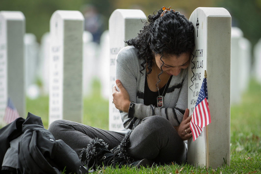 . Thania Sayne of Effingham, Ill., leans on the headstone at the grave of her husband, Army Sgt. Timothy D. Sayne, during the playing of taps at a nearby burial service at Arlington National Cemetery, in Arlington, Va., Wednesday, Oct. 16, 2013, a day before what would have been their third wedding anniversary.  Sayne, was 4 months pregnant with their second son, Douglas, when her husband was killed on Sept. 18, 2011, in the Kandahar province of Afghanistan.  (AP Photo/Manuel Balce Ceneta, File)