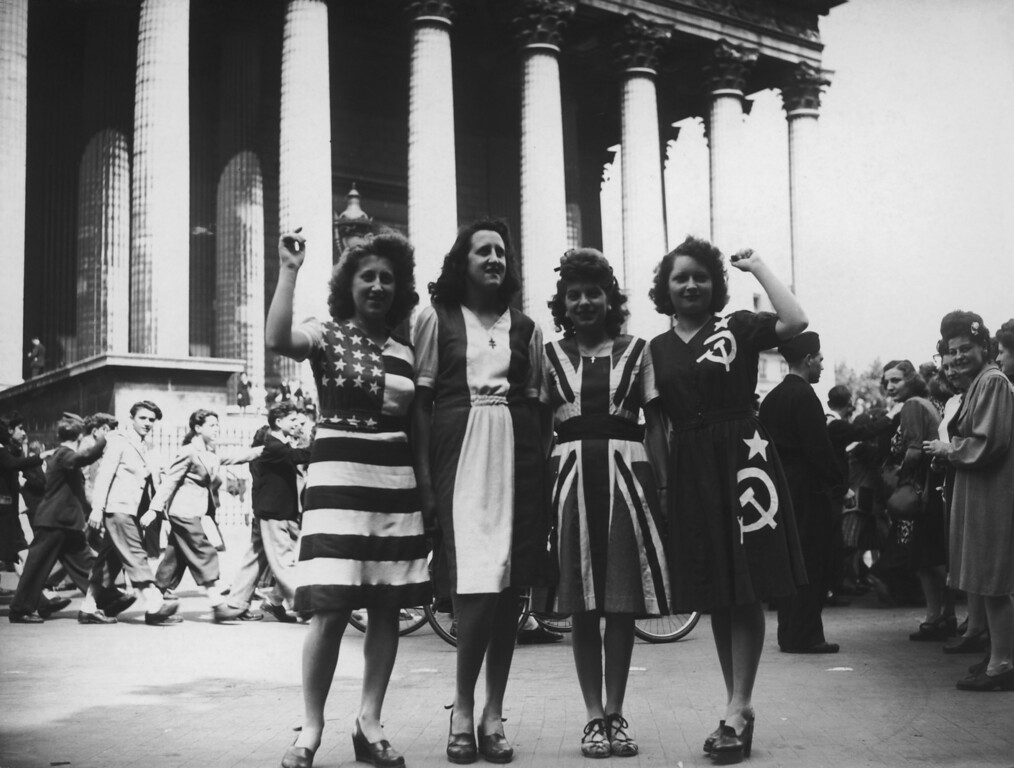. A group of women wearing dresses representing flags of the Allied powers (left to right: the USA, France, Britain and the Soviet Union) outside the Eglise de la Madeleine on VE Day in Paris, 8th May 1945. (Photo by Keystone/Hulton Archive/Getty Images)
