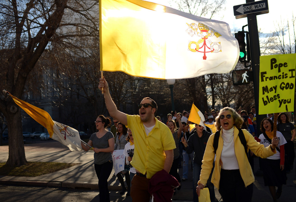 . DENVER, CO. - MARCH 13: Aaron Moss of Denver with flag of Vatican City, front, and people celebrate the election of new pope Francis I with a march from Civic Center to the Cathedral Basilica of the Immaculate Conception. Jorge Bergoglio of Argentina was elected new pope. March 13, 2013. Denver, Colorado. (Photo By Hyoung Chang/The Denver Post)