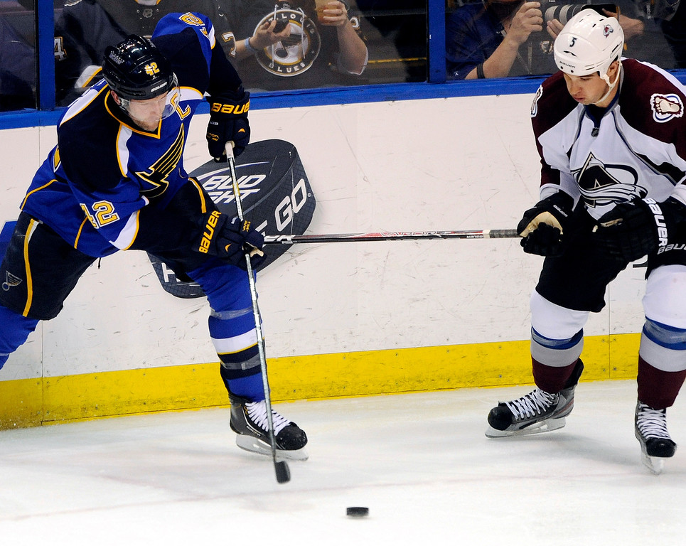 . St. Louis Blues\' David Backes (42) passes around Colorado Avalanche\'s Shane O\'Brien (5) in the second period of an NHL hockey game Tuesday, April 23, 2013, in St. Louis. (AP Photo/Bill Boyce)