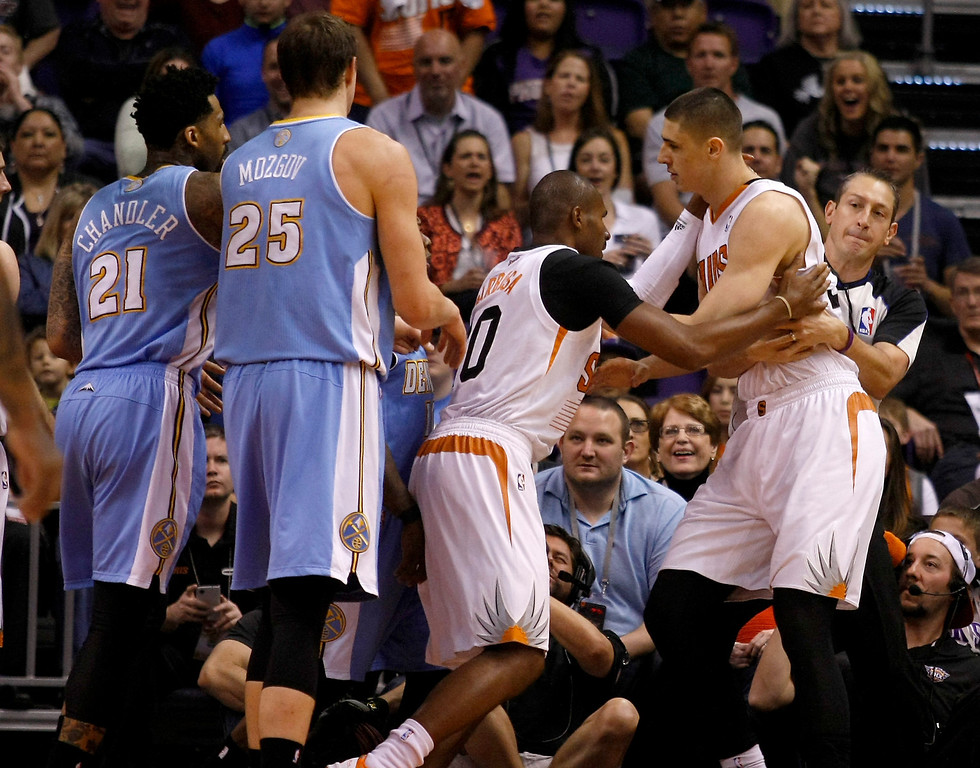 . Phoenix Suns center Alex Len (21) gets held back from Leandro Barbosa (10) after getting into a shoving match with players of the Denver Nuggets in the first quarter during an NBA basketball game, Sunday, Jan. 19, 2014, in Phoenix. (AP Photo/Rick Scuteri)