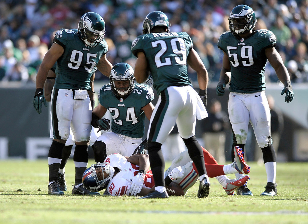 . New York Giants wide receiver Victor Cruz (80) reacts after being injured on a play as Philadelphia Eagles\' Mychal Kendricks (95), Bradley Fletcher (24), Nate Allen (29) and DeMeco Ryans (59) stand over him during the second half of an NFL football game Sunday, Oct. 27, 2013 in Philadelphia. (AP Photo/Michael Perez)