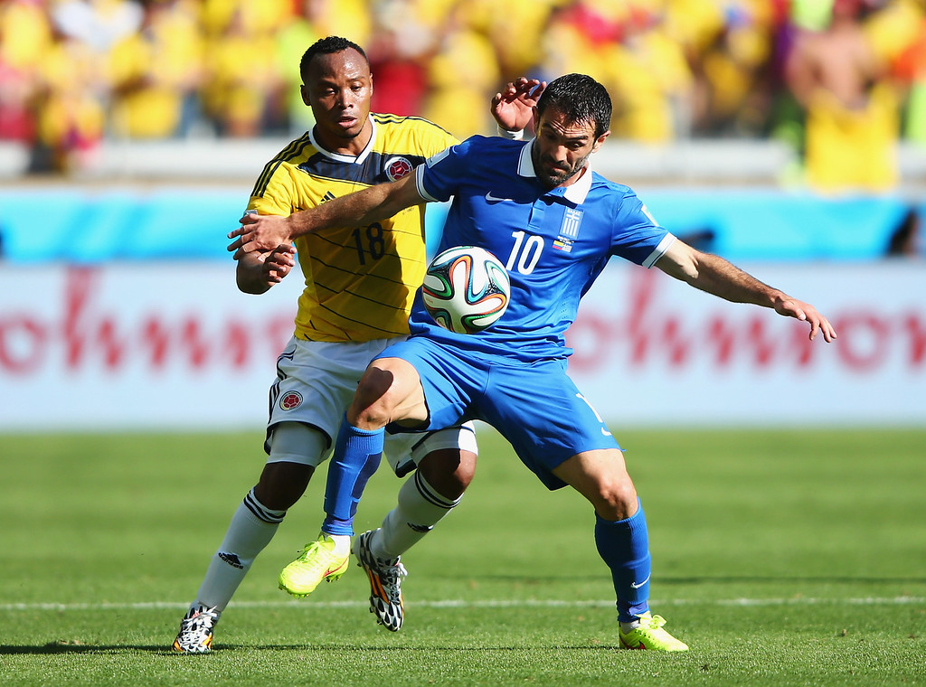 . Juan Camilo Zuniga of Colombia and Giorgos Karagounis of Greece battle for the ball during the 2014 FIFA World Cup Brazil Group C match between Colombia and Greece at Estadio Mineirao on June 14, 2014 in Belo Horizonte, Brazil.  (Photo by Ian Walton/Getty Images)