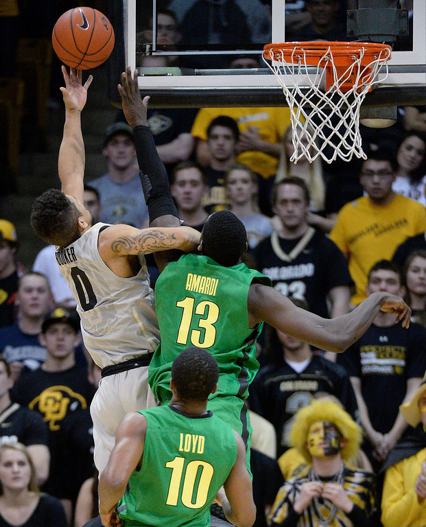 . Colorado Buffaloes guard Askia Booker (0) goes up for a shot pas Oregon Ducks forward Richard Amardi (13) during the first half January 5, 2014 at Coors Events Center. (Photo by John Leyba/The Denver Post)