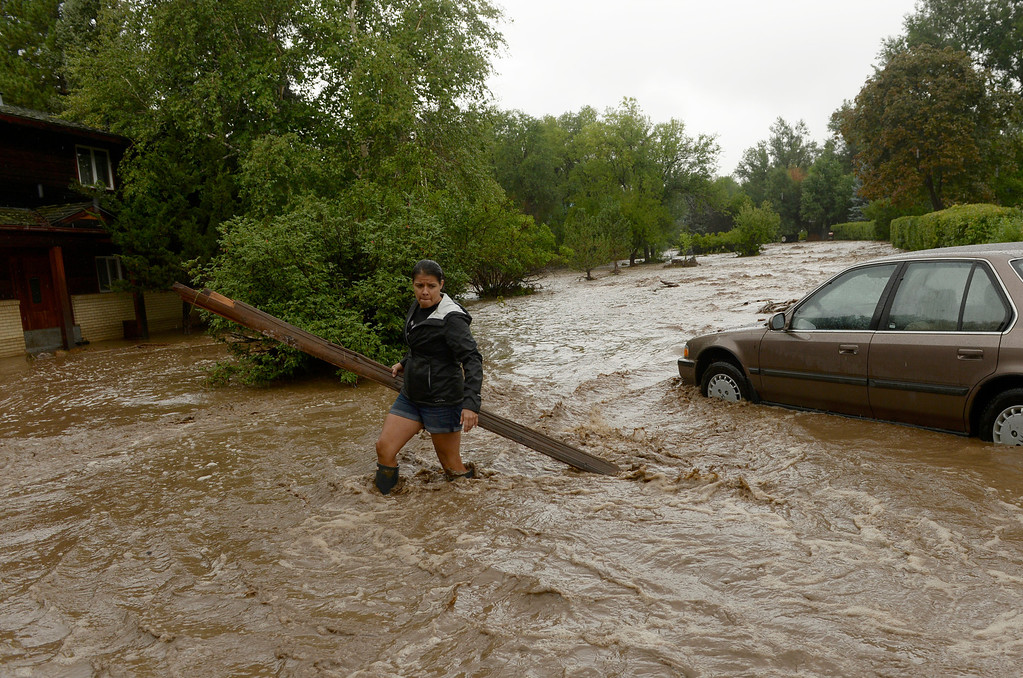 . BOULDER, CO - SEPTEMBER 12: Sonia Chacon clear debris from around her families home in north Boulder, September 12, 2013. Massive flash flooding is on going along the Front Range of Colorado. (Photo By RJ Sangosti/The Denver Post)