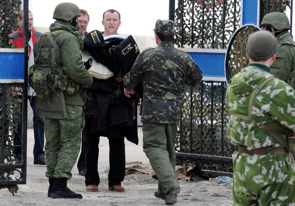 . Ukrainian officers leave the Ukrainian navy headquaters in Sevastopol as Russian soldiers stand guard on March 19, 2014. Ukrainian servicemen filed out of navy headquarters in Sevastopol on March 19 with tears in their eyes after the base was seized by pro-Moscow militants, Russian troops and Cossack forces. The assault began when some 200 unarmed militants -- some of them in balaclavas -- sawed through a fence and overran the base while the Ukrainian servicemen barricaded themselves inside. AFP PHOTO/  VIKTOR  DRACHEV/AFP/Getty Images
