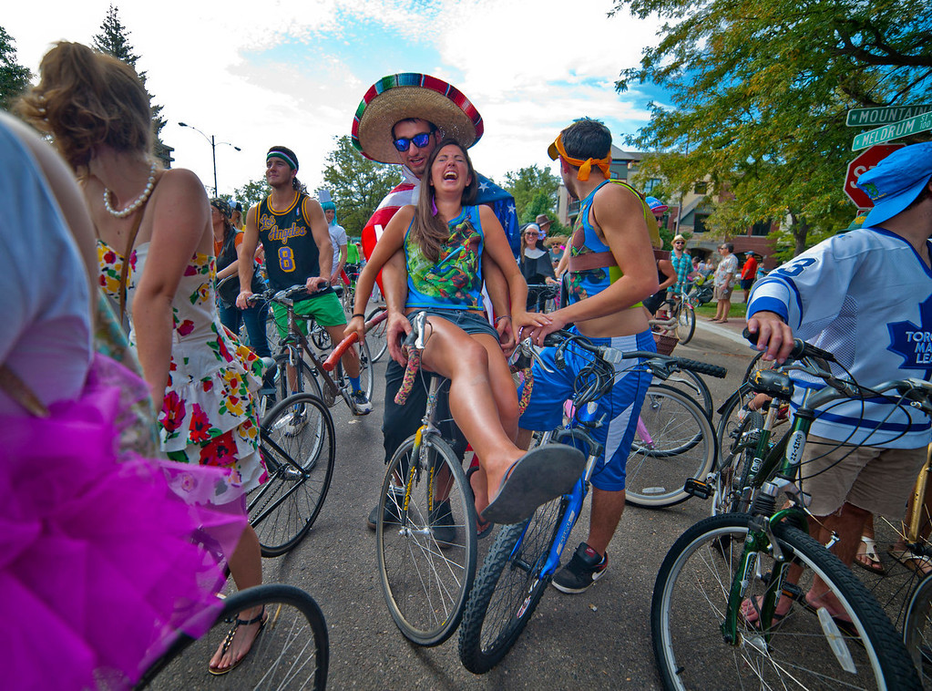 . Fort Collins, CO, U.S.A  Allyson Mitchell rides on the handle bars of friend Jeff Weaks at the start of the Tour de Fat at the intersection of Mountain St. and Meldrum St. in Fort Collins, Saturday August 31, 2013. The 14th annual Tour de Fat bike parade in Fort Collins had a record setting 25,000 participants.  The event benefits Overland Mountain Bike Club, Bike Fort Collins and Fort Collins Bike Co-op.   Photo by Evan Semón,