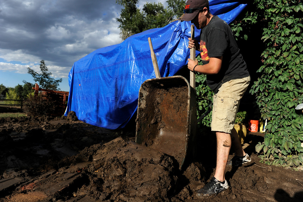 . Neighbor Weston Nassar dumps a wheelbarrow filled with mud from the back patio. Friends and neighbors of Shannon Rood jump in to help dig her dig out on her property on N. 73rd St. and Nimbus Road west of Hwy 119. Rood had over two feet of mud in some places. (Photo By Kathryn Scott Osler/The Denver Post)