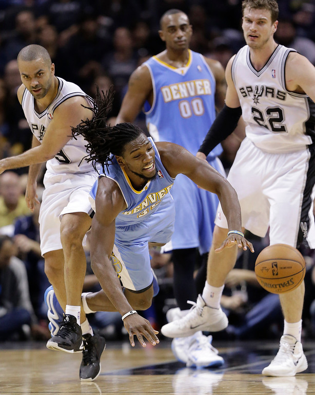 . Denver Nuggets\' Kenneth Faried (35) tumbles to the court as he and  San Antonio Spurs\' Tony Parker (9) and Tiago Splitter (22) raced for a loose ball during the second half of an NBA basketball game, Wednesday, March 26, 2014, in San Antonio. San Antonio won 108-103. (AP Photo/Eric Gay)