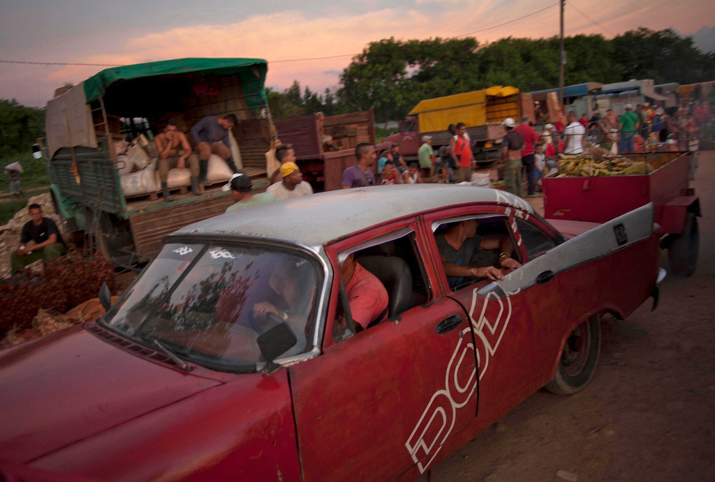 . In this Sept. 25, 2013 photo, a merchant drives away his classic American car pulling a small trailer loaded with bananas, tomatoes and onions at the 114th Street Market on the outskirts of Havana, Cuba. Produce is brought in by growers themselves and by transportation specialists who make a living by buying crops far away and hauling them to Havana, the island\'s biggest and most important market. (AP Photo/Ramon Espinosa)