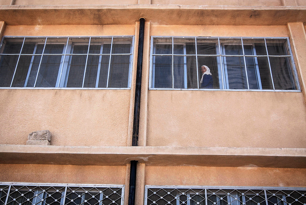. In this Thursday, Sept. 26, 2013 photo, a Syrian girl looks out of a window of the public school in Madaya village as classes begin in the Idlib province countryside of Syria. Millions of Syrian children most of them in government-controlled areas have returned to school in the past two weeks, despite the conflict that according to UNICEF has left 4,000 Syrian schools or one in five damaged, destroyed or sheltering displaced families. (AP Photo)