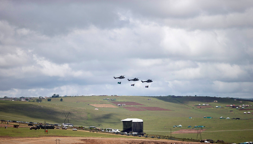. Three helicopters fly over the grave during the burial of former South African President Nelson Mandela in his hometown Qunu, South Africa, Sunday Dec. 15, 2013. (AP Photo/Peter Dejong)