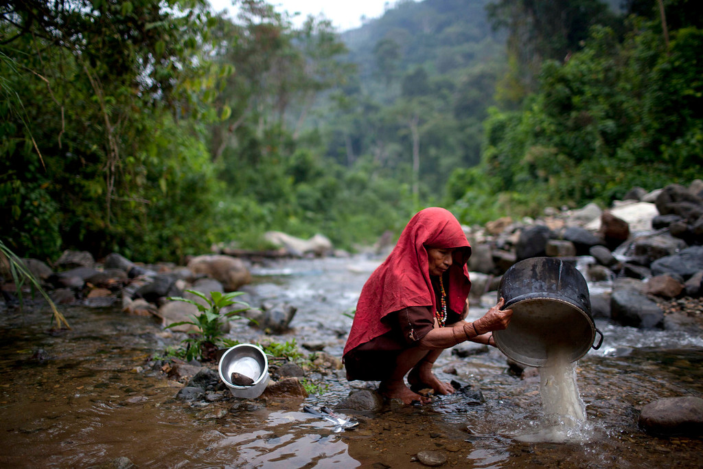 . In this Oct. 1, 2013 photo, an Ashaninka Indian woman washes a pot in a stream in Kitamaronkani, Pichari district, Peru. Peru\'s Ashaninka Indians share the world\'s top coca-growing valley with drug traffickers, rebels, illegal loggers and, now, an increased military presence. The government is now boosting its military footprint in the valley in a bid to fight Shining Path remnants and the drug traffickers they protect. (AP Photo/Rodrigo Abd)