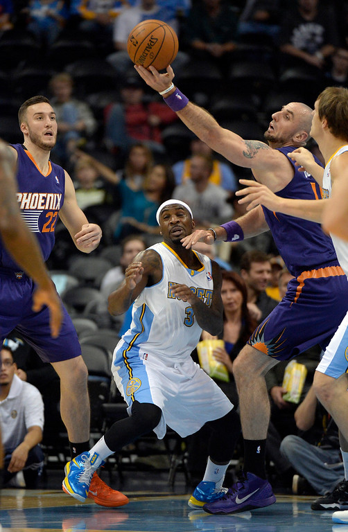 . Phoenix Suns center Marcin Gortat (4) reaches out for a rebound over Denver Nuggets point guard Ty Lawson (3) during the first quartet October 23, 2013 at Pepsi Center. (Photo By John Leyba/The Denver Post)