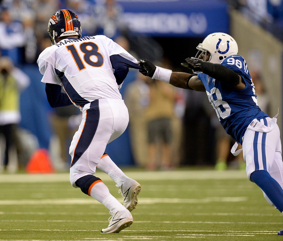 . Indianapolis Colts outside linebacker Robert Mathis (98) pulls Denver Broncos quarterback Peyton Manning (18) by the jersey but can\'t hang on during the first quarter October 20, 2013 at Lucas Oil Field. Photo by John Leyba/The Denver Post)