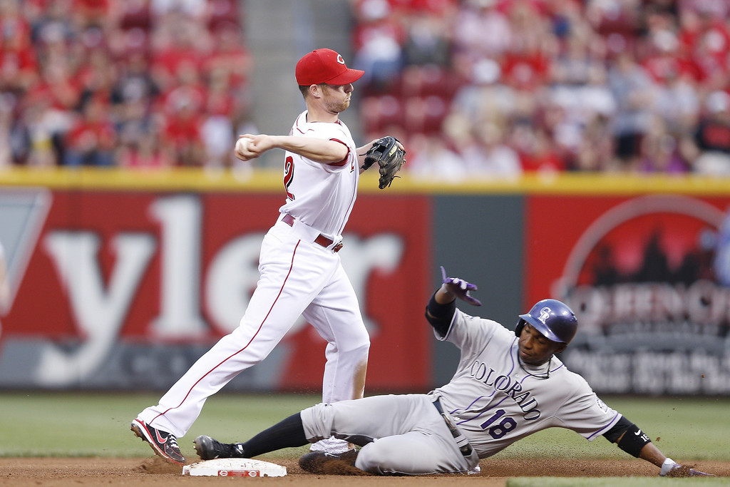 . Zack Cozart #2 of the Cincinnati Reds turns a double over Jonathan Herrera #18 of the Colorado Rockies during the game at Great American Ball Park on June 5, 2013 in Cincinnati, Ohio. (Photo by Joe Robbins/Getty Images)