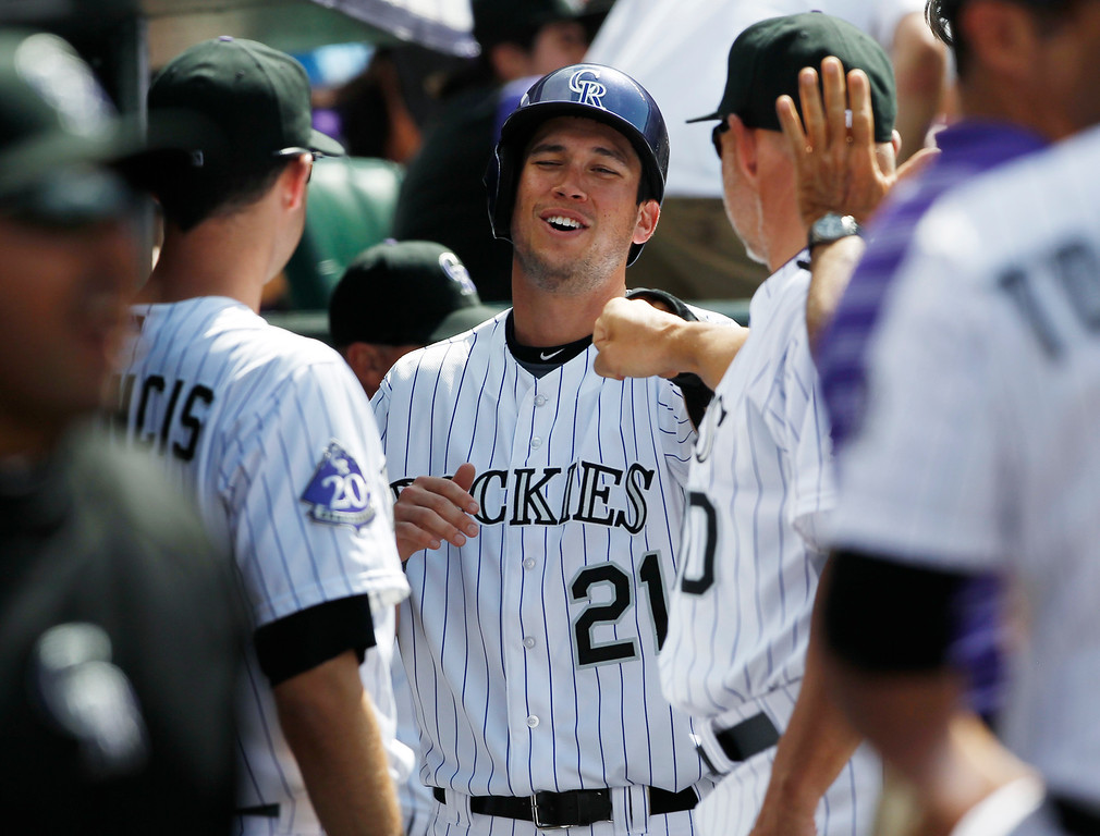 . Colorado Rockies\' Tyler Colvin, center, is congratulated by teammate Jeff Francis, left, and coach Dante Bichette after scoring on an RBI-single by Tyler Chatwood against the Philadelphia Phillies in the fourth inning of a baseball game in Denver, Saturday, June 15, 2013. (AP Photo/David Zalubowski)