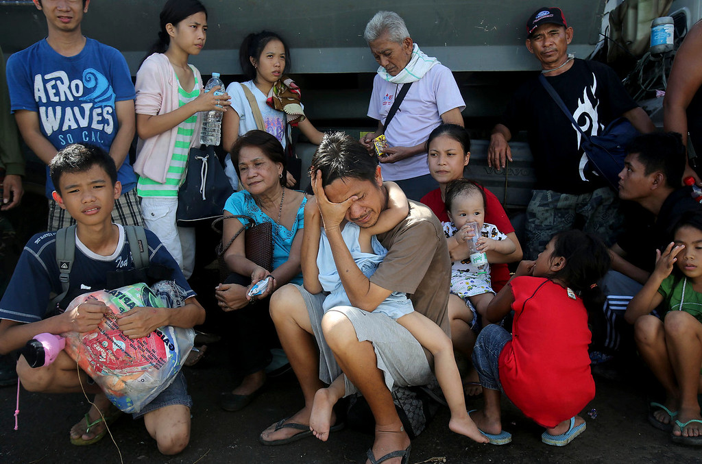 . Survivors of Typhoon Haiyan wait patiently to be evacuated on a C-130 cargo plane at the airport Wednesday, Nov. 13, 2013 in Tacloban city, Leyte province, central Philippines. Typhoon Haiyan, one of the strongest storms on record, slammed into six central Philippine islands on Friday leaving a wide swath of destruction. (AP Photo/Wong Maye-E)
