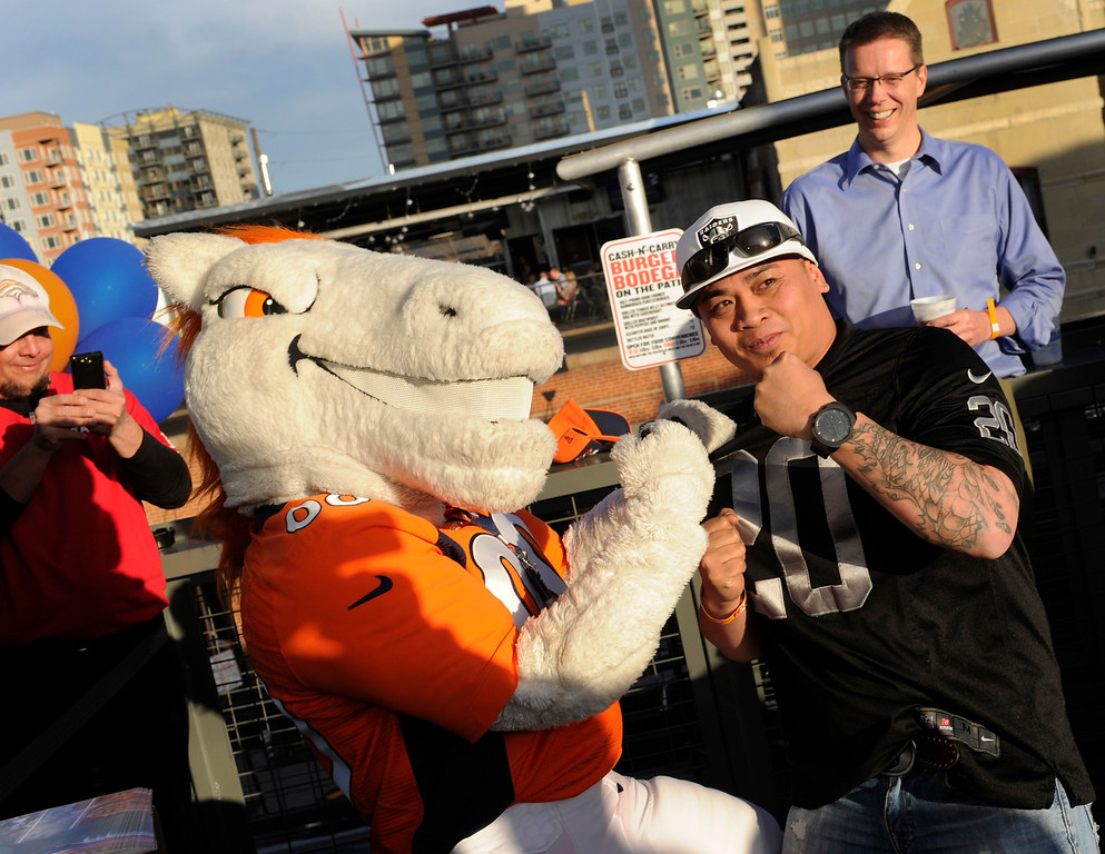 . Raiders fan Percy Weitzel, right, hammed it up with Denver Broncos mascot Miles on the rooftop deck of the Tavern Downtown Thursday night. Broncos fans gathered for a NFL draft party at the Tavern Downtown, 1949 Market Street, Thursday night, April 25, 2013. Photo By Karl Gehring/The Denver Post