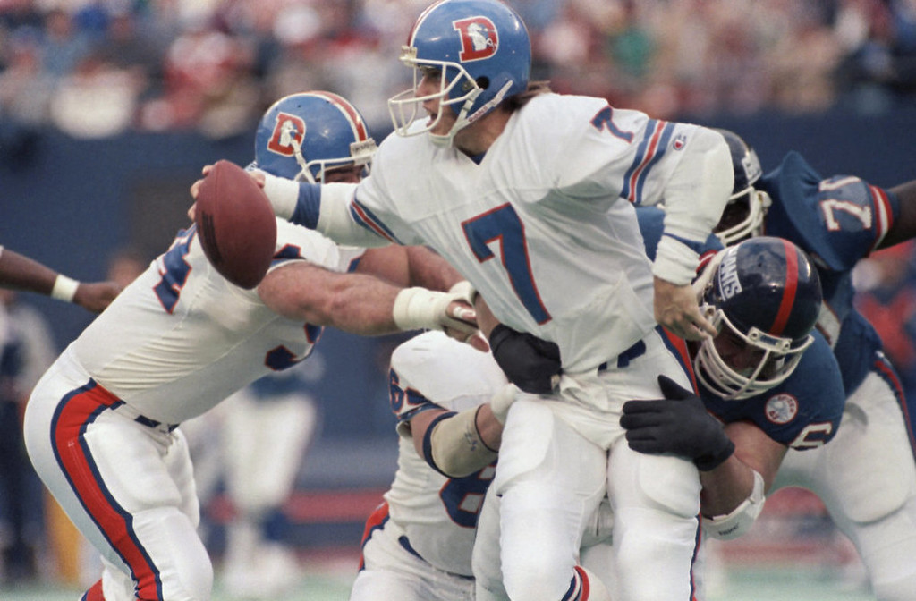 . Denver Broncos quarterback John Elway (7) looks to get rid of the football as he caught for a sack by the New York Giants Jim Burt during second quarter NFL action at Giants Stadium, Sunday, Nov. 23, 1986, East Rutherford, N.J. (AP Photo/Bill Kostroun)