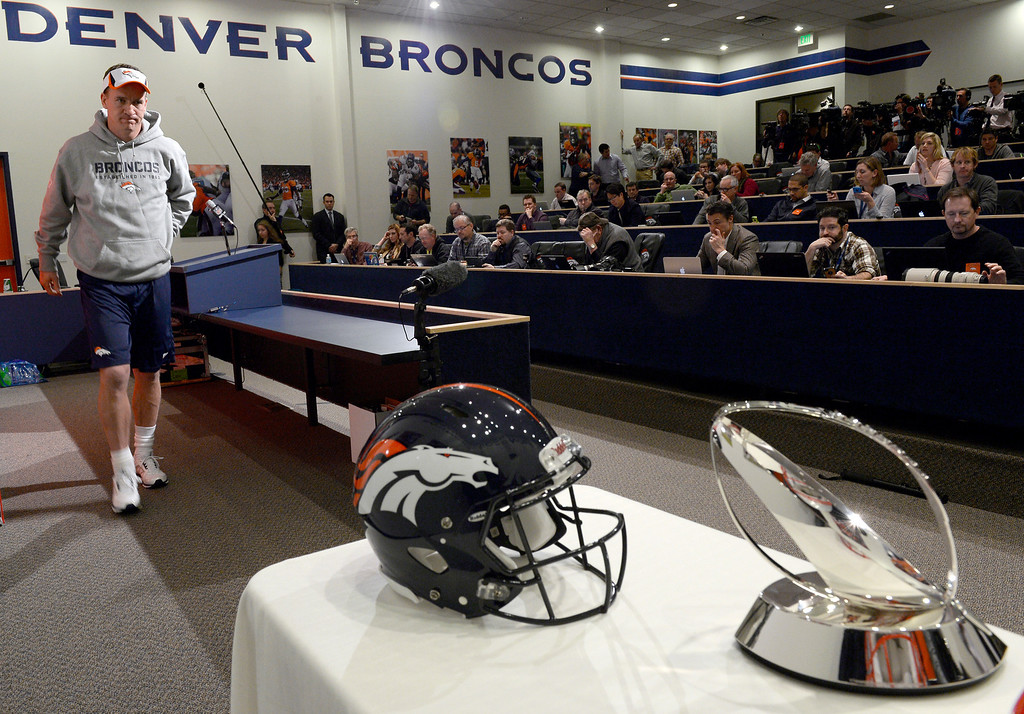 . Denver Broncos quarterback Peyton Manning (18) walks off from the podium after his press conference. The NFL provided the Lamar Hunt Trophy along with the New England Patriots helmet and Denver Broncos helmet during press conferences January 15, 2014 at Dove Valley. The Lamar Hunt Trophy goes to the winner of the AFC Championship game. (Photo by John Leyba/The Denver Post)