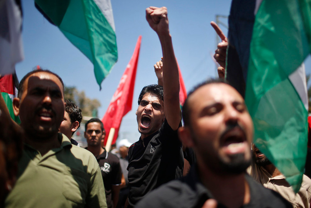 . Palestinians chant slogans during a protest against resuming peace talks with Israel, in Gaza City July 28, 2013. Israel was expected on Sunday to approve releasing more than 100 Arab prisoners as a step to renew stalled peace talks with the Palestinians ahead of plans to convene negotiators in Washington later this week. REUTERS/Mohammed Salem