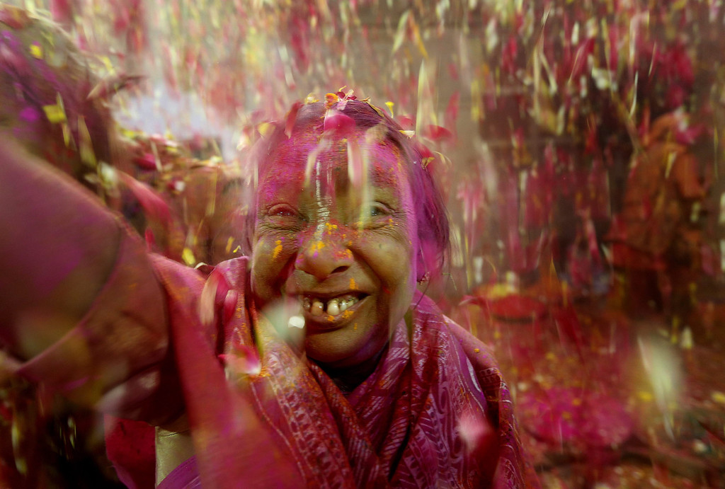 . An Indian widow throws petals while participating in the Holi festival in Vrindavan, Uttar Pradesh, India, March 14, 2014. For the first time, about a 1,000 widows of Vrindavan played Holi with colors at an ashram. The event was organized by Indian NGO Sulabh International as at the behest of the Supreme Court. Sulabh International is trying to improve the condition of widows who are living in government shelter homes.  EPA/HARISH TYAGI