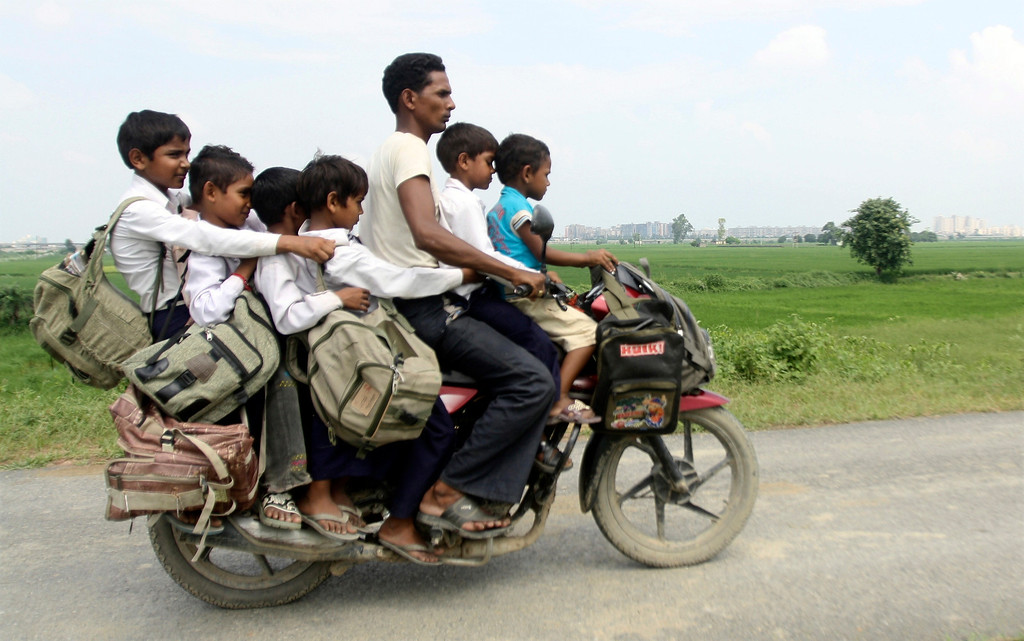 . A man rides a motorcycle carrying six children on their way back home from school at Greater Noida in the northern Indian state of Uttar Pradesh September 10, 2010. REUTERS/Parivartan Sharma