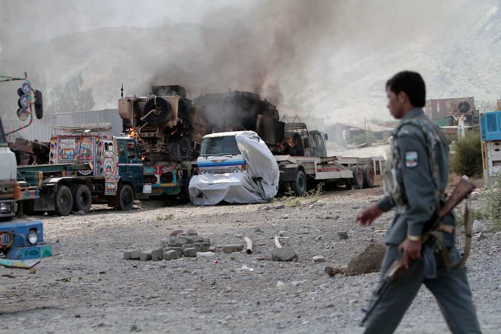 . An Afghan policeman walks near burning NATO supply trucks following an attack by militants in the Torkham area near the Pakistan-Afghanistan border in Jalalabad province east of Kabul, Afghanistan, Monday, Sept. 2, 2013. The Taliban claimed responsibility for the strike on a U.S. base in Afghanistan near the border with Pakistan on Monday, setting off bombs, torching vehicles and shutting down a key road used by NATO supply trucks, officials said. Several people were killed.   (AP Photo/Rahmat Gul)