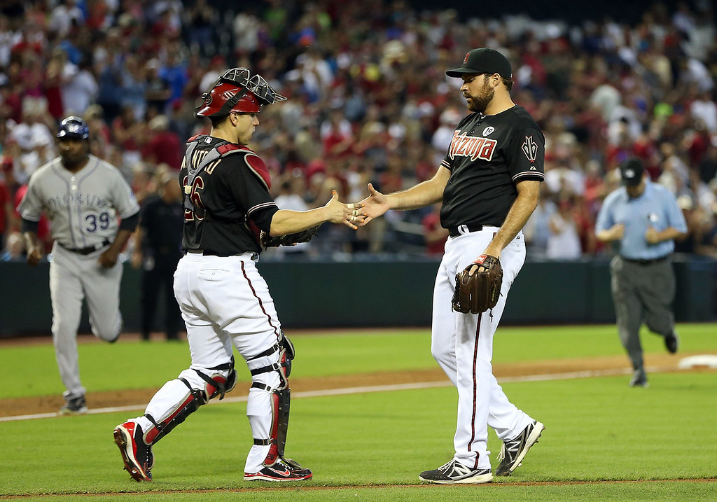 . Relief pitcher Josh Collmenter #55 of the Arizona Diamondbacks celebrates with catcher Miguel Montero #26 after defeating the Colorado Rockies in the MLB game at Chase Field on July 7, 2013 in Phoenix, Arizona.  The Diamondbacks defeated the Rockies 6-1.  (Photo by Christian Petersen/Getty Images)