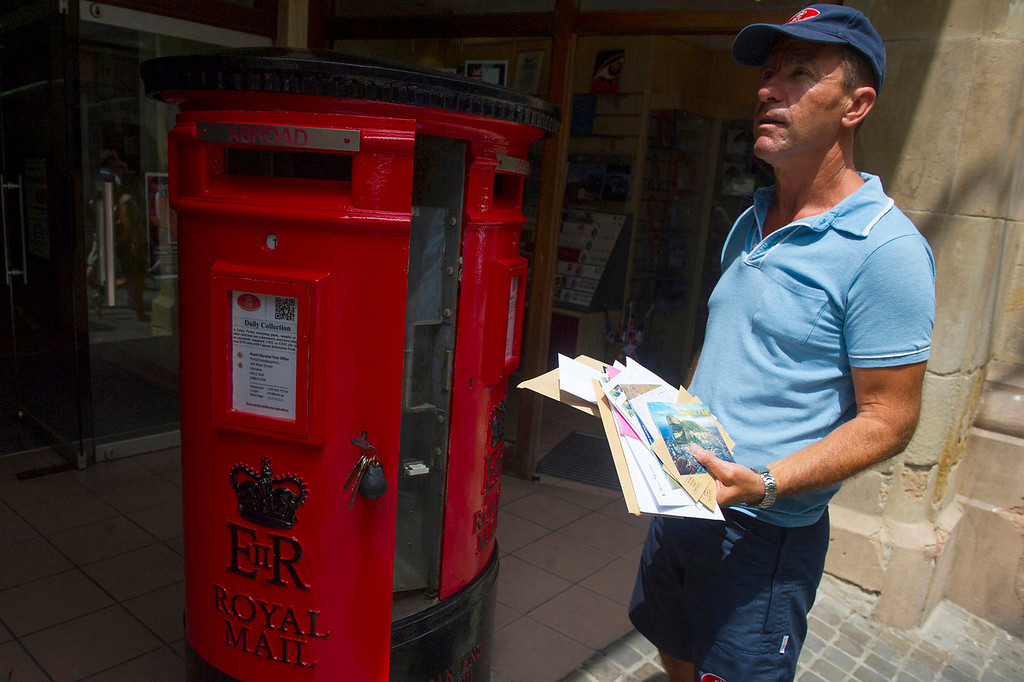 . A Royal Mail employee gathers the contents of a mailbox in Gibraltar on August 13, 2013. This rock of seven square kilometers enclosed in the coast of Andalusia, off the tip of southern Spain, is reminiscent of England: the red phone booths, mailboxes Royal Mail, the lampposts decorated with flowers, and double decker buses.   MARCOS MORENO/AFP/Getty Images
