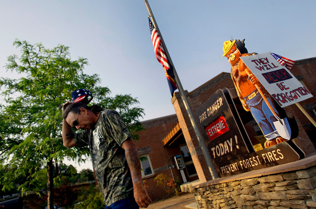 . Retired firefighter Roger (did not provide his last name), reacts after placing a sign (R) outside Fire Station No. 1 in Prescott, Arizona June 30, 2013.  REUTERS/Joshua Lott