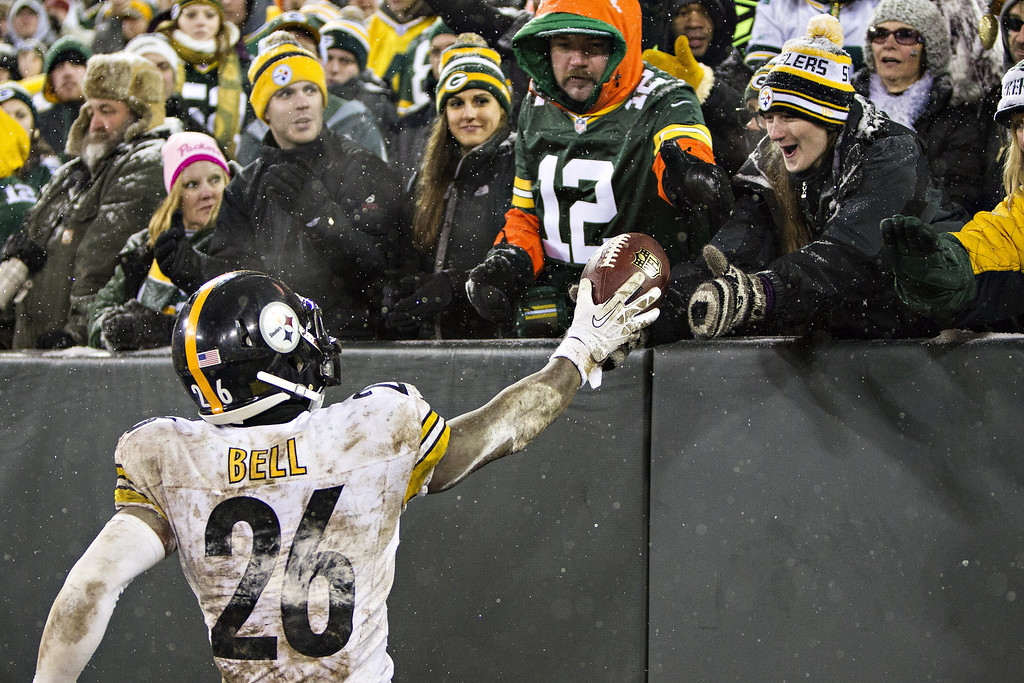 . Le\'Veon Bell #6 of the Pittsburgh Steelers hands the ball to a fan after scoring the winning touchdown against the Green Bay Packers at Lambeau Field on December 22, 2013 in Green Bay, Wisconsin.  The Steelers defeated the Packers 38-31.  (Photo by Wesley Hitt/Getty Images)