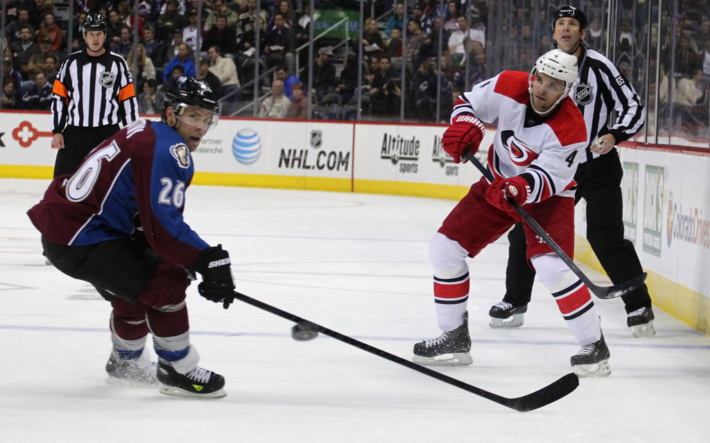 . Carolina Hurricanes defenseman Andrej Sekera (4), of Slovakia, sends a pass over the stick of Colorado Avalanche center Paul Stastny (26) in the second period of an NHL hockey game in Denver on Friday, Oct. 25, 2013.(AP Photo/Joe Mahoney)