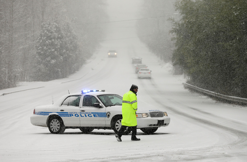 . A police officer prepares to close a road as a winter storm moves into the area Wednesday, Feb. 12, 2014, in Charlotte, N.C. (AP Photo/Chuck Burton)