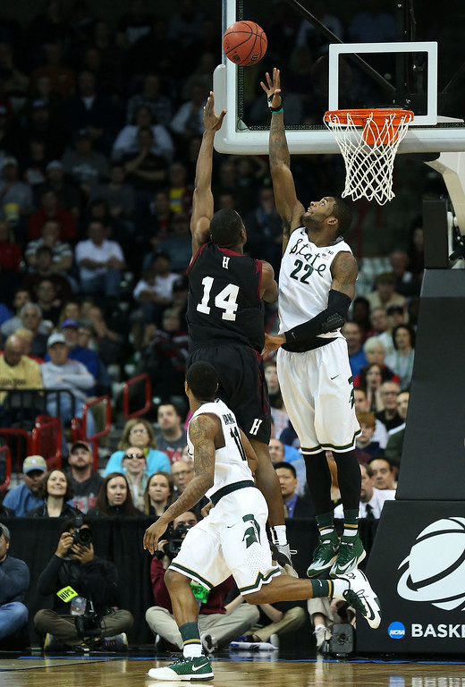 . SPOKANE, WA - MARCH 22:  Steve Moundou-Missi #14 of the Harvard Crimson shoots against Branden Dawson #22 of the Michigan State Spartans in the second half during the Third Round of the 2014 NCAA Basketball Tournament at Spokane Veterans Memorial Arena on March 22, 2014 in Spokane, Washington.  (Photo by Stephen Dunn/Getty Images)